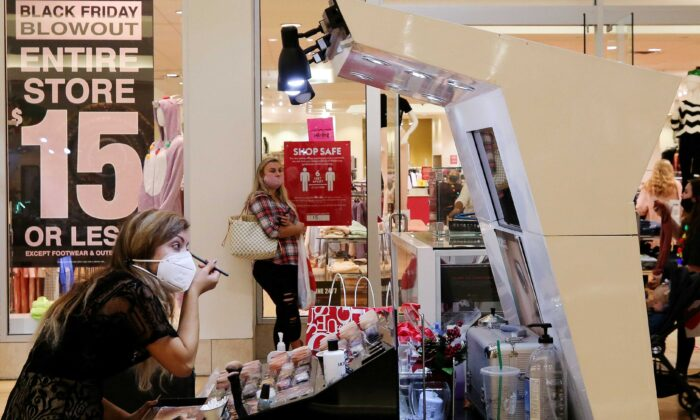 An employee wearing a protective mask applies makeup at Coastal Grand Mall on Black Friday, in Myrtle Beach, S.C., on Nov. 27, 2020. (Micah Green/Reuters)