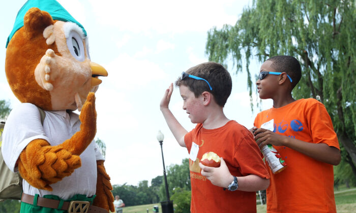 Child hi-fives the icon of U.S. Forest Service, Woodsy the Owl (L), at the Constitution Gardens Pond of the National Mall in Washington on June 6, 2011. (Alex Wong/Getty Images)