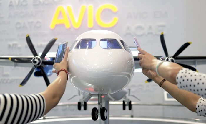 Visitors take photos of a MA700 plane model designed by Aviation Industry Corporation of China (AVIC) at the Beijing International Aviation Expo in Beijing on Sept. 17, 2015. (Wang Zhao/AFP via Getty Images)