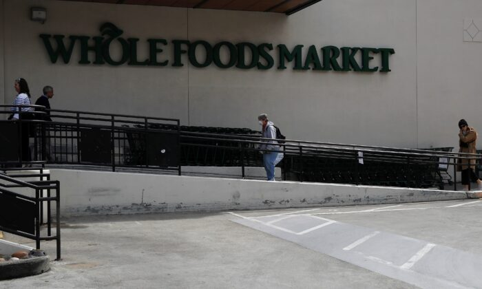 People wait in line practicing social distance at a Whole Foods Market amid an outbreak of COVID-19, in San Francisco, Calif., on March 31, 2020. (Shannon Stapleton/Reuters)