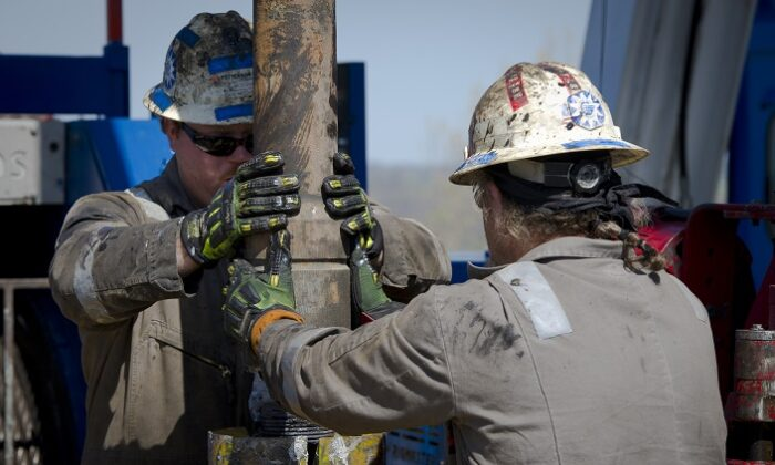 Workers change pipes at Consol Energy Horizontal Gas Drilling Rig exploring the Marcellus Shale outside the town of Waynesburg, Pa., on April 13, 2012. (MLADEN ANTONOV/AFP via Getty Images)