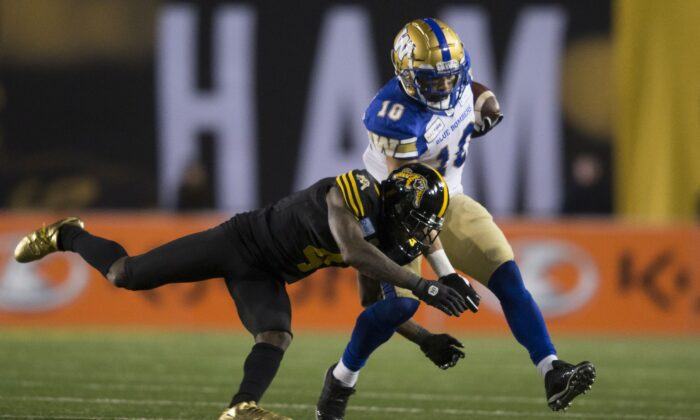 Hamilton Tiger-Cats' Richard Leonard tackles Winnipeg Blue Bombers' Nic Demski during the 107th Grey Cup in Calgary on Nov. 24, 2019. (The Canadian Press/Todd Korol)