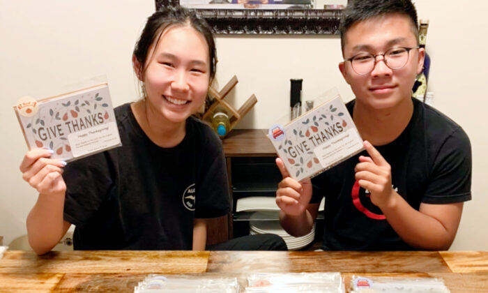 Siblings Karis and Kyler Choi hold up handcrafted Christmas cards for seniors. (Courtesy of Karis and Kyler Choi)