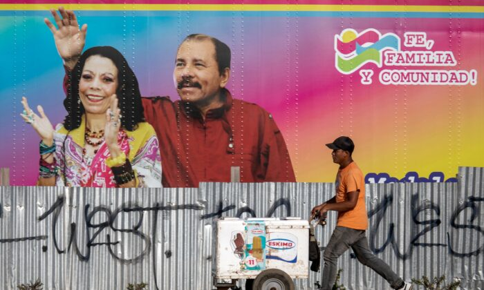 An ice cream vendor walks by a mobile health clinic displaying a picture of Nicaragua's President Daniel Ortega (R) and his wife Vice-President Rosario Murillo (R) in Managua on April 14, 2020 during the pandemic of the novel coronavirus COVID-19.  (INTI OCON/AFP via Getty Images)