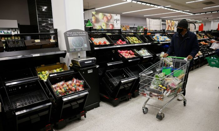 A shopper wearing a face mask pushes a trolley past empty fruit and vegetable troughs inside an ASDA supermarket in Walthamstow in northeast London, on Dec. 22, 2020. (Tolga Akmen /AFP via Getty Images)