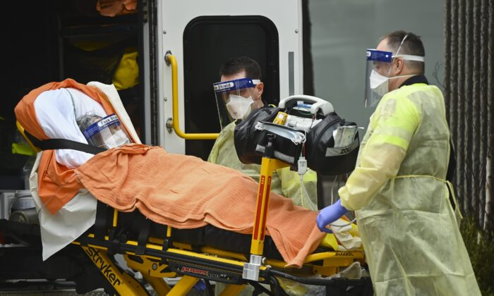 Paramedics take away an elderly patient at the Tendercare Living Centre, long-term-care facility during the COVID-19 pandemic in Scarborough, Ont., Canada on Dec. 23, 2020. (Nathan Denette/The Canadian Press)