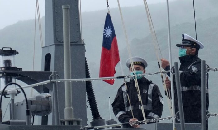 Two navy soldiers raise Taiwan's national flag during an official ceremony at a shipyard in Su'ao, a township in eastern Taiwan's Yilan County, on Dec. 15, 2020. (Sam Yeh/AFP via Getty Images)