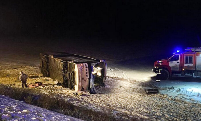 This photo provided by the Government of Ryazan Region of Russia Press Office shows a bus which fell off a road near Vysokoye village, Russia, early Friday, Dec. 25, 2020.(Government of Ryazan Region of Russia Press Office via AP)
