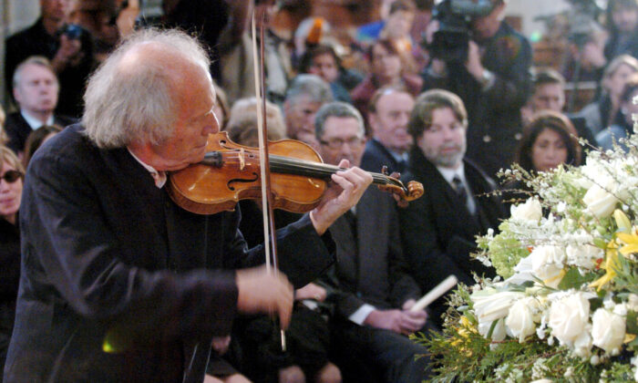 In this April 3 2004, Israeli violinist Ivry Gitlis, ambassador to the UNESCO, plays at the funeral ceremony of Oscar-winning British actor and play-writer, Sir Peter Ustinov, in the cathedral St. Pierre, in Geneva, Switzerland. (Martial Trezzini/Pool Photo via AP, File)