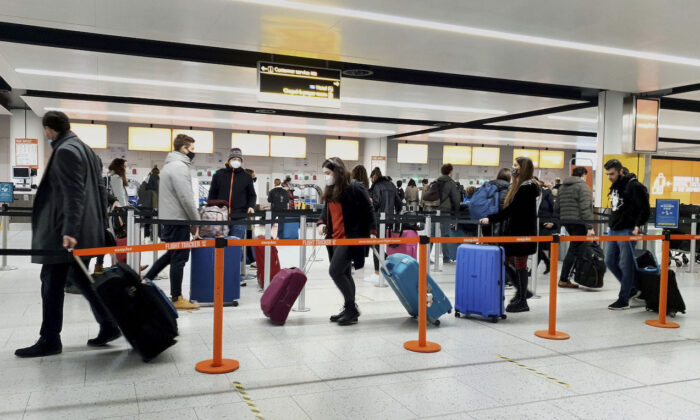 Passengers queue for check-in at Gatwick Airport in West Sussex, England, south of London, on Dec. 20, 2020. (Gareth Fuller/PA via AP)