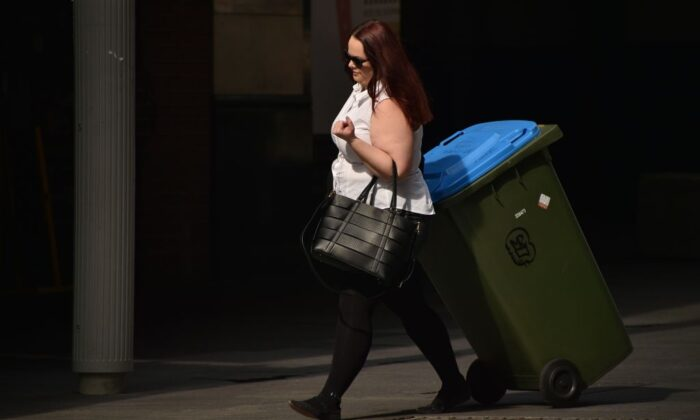 "A woman pulls a ""wheelie bin"" on a street in the central business district of Sydney on May 8, 2018. (PETER PARKS/ Getty Images)"