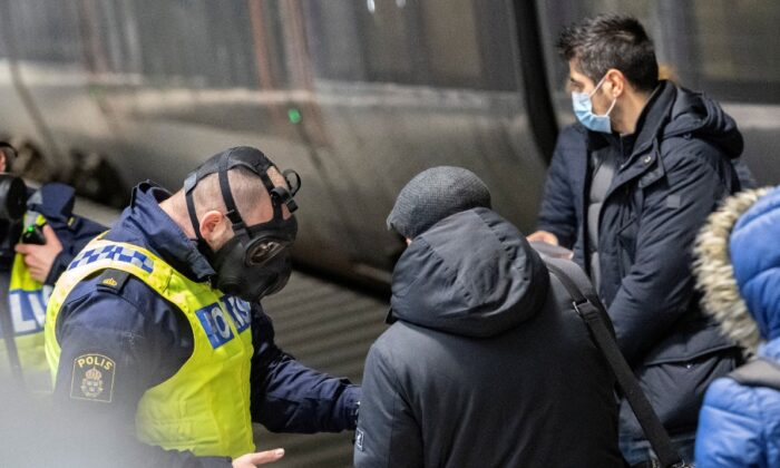 Travelers from Denmark are met by Swedish police in protective masks at the border control point at Hyllie station, as the Swedish government shut the border after a mutated strain of the coronavirus was discovered in Denmark, in Malmo, Sweden on Dec. 22, 2020. (Johan Nilsson/TT News Agency via Reuters)