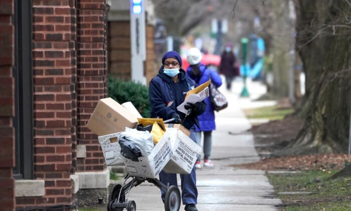 A U.S. postal worker delivers packages, boxes, and letters Tuesday along her route in the Hyde Park neighborhood of Chicago, Dec. 22, 2020, just three days before Christmas. (Charles Rex Arbogast/AP Photo)