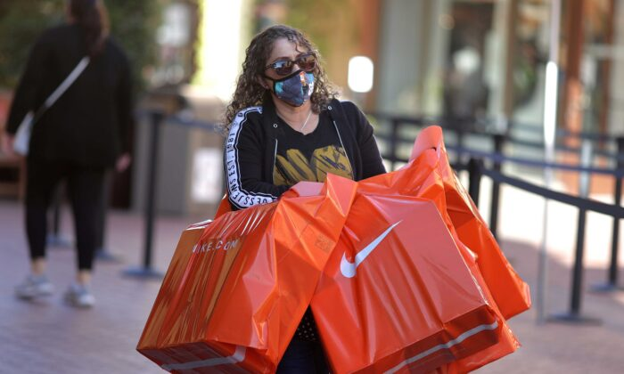 A woman carries Nike shopping bags at the Citadel Outlet mall in Commerce, Calif., on Dec. 3, 2020. (Lucy Nicholson/Reuters)