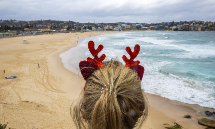 A woman wearing antlers looks at Bondi Beach in Sydney, Australia on Dec. 25, 2020. (Jenny Evans/Getty Images)
