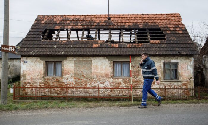 A man walks next to a damaged house after a 5.2 magnitude earthquake, in Brest Pokupski village, Croatia, on Dec. 28, 2020. (Antonio Bronic/Reuters)