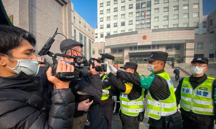 Police attempt to stop journalists from recording footage outside the Shanghai Pudong New District People's Court, where citizen journalist Zhang Zhan was sentenced, in Shanghai, on Dec. 28, 2020. (Leo Ramirez/AFP via Getty Images)