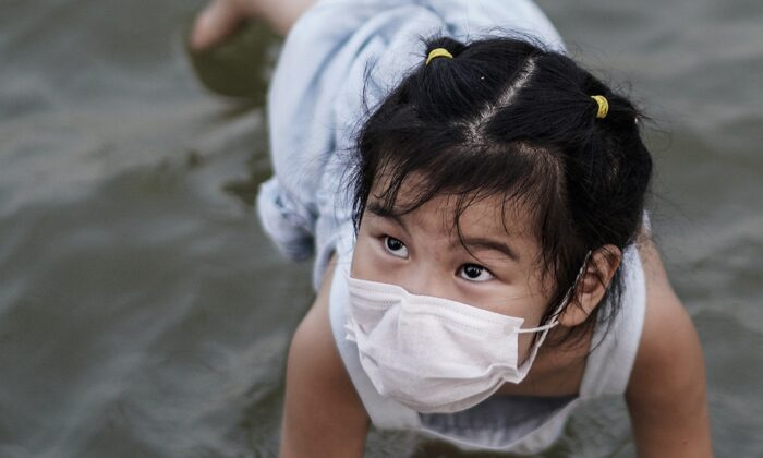 A girl plays in a flooded Jiangtan park in Wuhan, China on June 30, 2020. (Getty Images)
