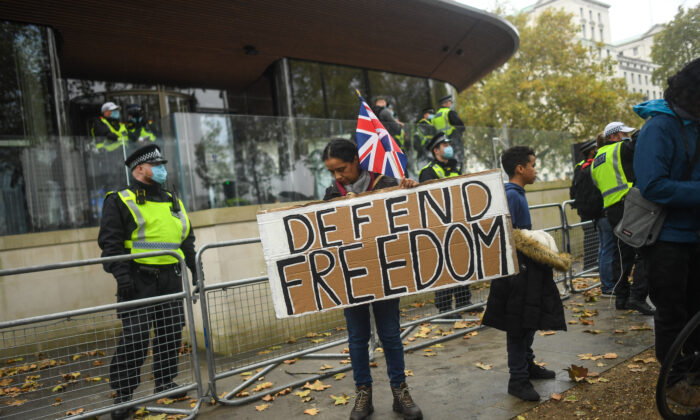 A protester holds a sign reading 'Defend Freedom' during a Unite for Freedom march outside New Scotland Yard on Oct. 24, 2020, in London. Hundreds of anti-mask and anti-lockdown protesters marched through central London demonstrating against latest coronavirus lockdown measures. (Photo by Peter Summers/Getty Images)