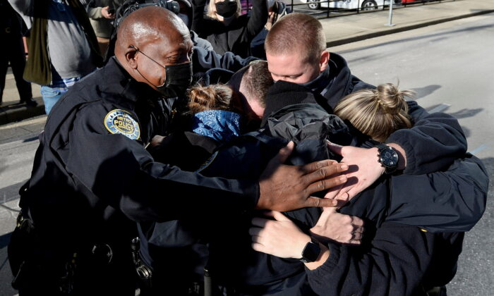 Nashville Metro Police Chief John Drake (L) and officers Amanda Topping, Michael Sipos, James Luellen, Brenna Hosey, and James Wells embrace after a news conference held to discuss the Christmas Day explosion in Nashville, Tenn., on Dec. 27, 2020. (Mark Zaleski/The Tennessean/USA Today Network via Reuters)