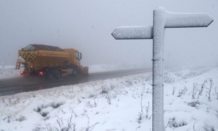 In this file image, a signpost marking the Pennine Way footpath is covered with snow as a gritting lorry drives along the A62 above the village of Delph, in northern England, on Dec. 4, 2020. (Oli Scarff/AFP via Getty Images)
