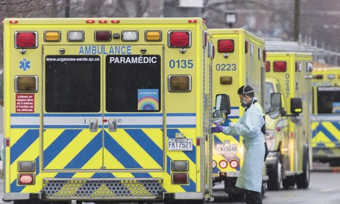 A paramedic stands next to an ambulance outside a hospital in Montreal on Dec. 28, 2020. (The Canadian Press/Graham Hughes)