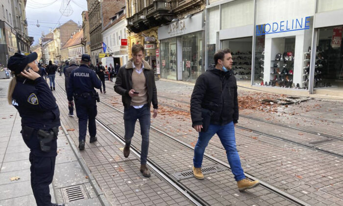Residents walk past debris caused by an earthquake in downtown Zagreb, Croatia, on Dec. 29, 2020. A strong earthquake hit Croatia on Tuesday, with some injuries reported as well as considerable damage to roofs and buildings southeast of the capital. (Filip Horvat/AP Photo)