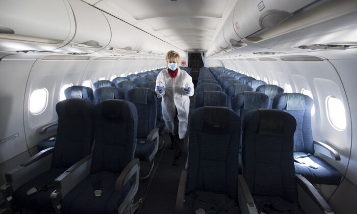 A flight attendant wears personal protective equipment as she walks through the back part of a near empty plane traveling from Calgary to Vancouver, Canada, on June 9, 2020.  (Jonathan Hayward/The Canadian Press)