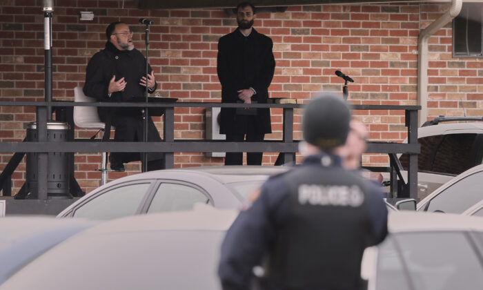 An Aylmer police officer videotapes as Pastor Henry Hildebrandt speaks during a drive-in service at The Church of God in Aylmer, Ontario, Canada, on April 26, 2020. (Geoff Robins/The Canadian Press)