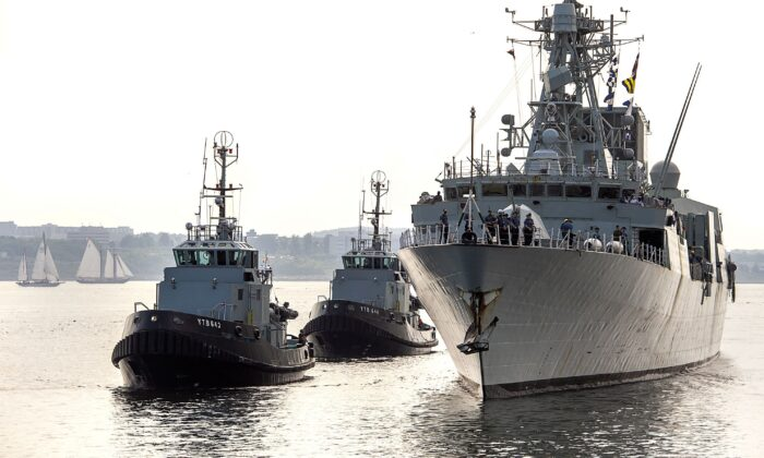 HMCS Fredericton, guided by tugs, returns to Halifax on July 28, 2020, after completing a six-month deployment in the Mediterranean Sea. (The Canadian Press/Andrew Vaughan)