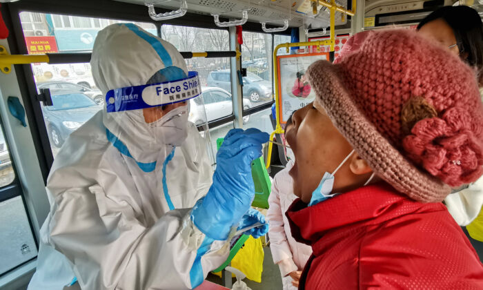 A health worker takes a swab from a resident to test for the COVID-19 in Dalian, China on Dec. 23, 2020. (STR/AFP via Getty Images)