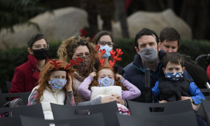 A family wears protective masks in Garden Grove, Calif., on Dec. 24, 2020. (Patrick T. Fallon / AFP via Getty Images)