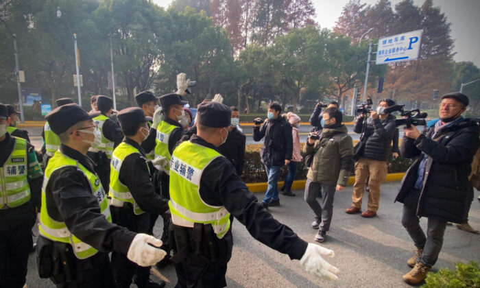 Police attempt to stop journalists from recording footage outside the Pudong New District People's Court in Shanghai, on Dec 28, 2020. (Leo Ramirez/AFP via Getty Images)