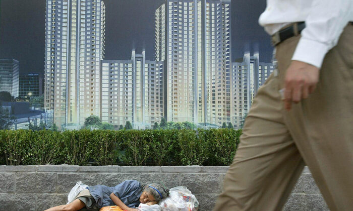 A homeless woman sleeps with her belongings beneath an advertising billboard promoting new urban development in Beijing on Aug. 21, 2003. (Frederic J. Brown/AFP via Getty Images)