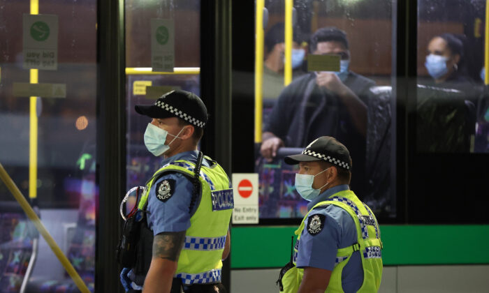 Passengers from Qantas flight QF583 are escorted to waiting Transperth buses by Police Officers after being processed following their arrival at Perth Airport. (Paul Kane/Getty Images)