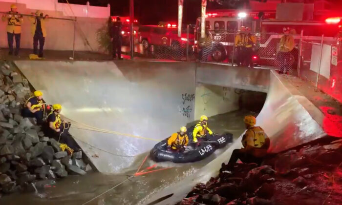 Members of the Orange County Fire Authority prepare to rescue two adults trapped in flowing water beneath an overpass in Santa Ana, Calif., on Dec. 28, 2020. (Screenshot/Twitter/Orange County Fire Authority)