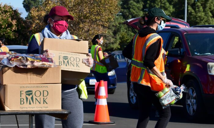 Food is loaded as drivers in their vehicles wait in line on arrival at a food distribution hosted by the Los Angeles Food Bank in Hacienda Heights, Calif., on Dec. 4, 2020. (Frederic J. Brown/AFP via Getty Images)