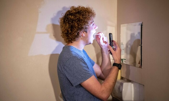A student performs a university-provided CCP virus lateral flow test on himself in his college room in Oxford, England, on Dec.12, 2020. (Laurel Chor/Getty Images)