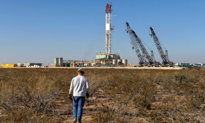 An oil worker walks toward a drill rig after placing ground monitoring equipment in the vicinity of the underground horizontal drill in Loving County, Texas, on Nov. 22, 2019. (Angus Mordant/Reuters)