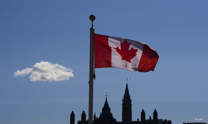Parliament Hill is viewed below a Canada flag in Gatineau, Quebec, on Sept. 18, 2020. (THE CANADIAN PRESS/Sean Kilpatrick)