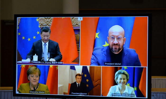 European Commission President Ursula von der Leyen, European Council President Charles Michel, German Chancellor Angela Merkel, French President Emmanuel Macron, and Chinese leader Xi Jinping are seen on a screen during a video conference, in Brussels, on Dec. 30, 2020. (Johanna Geron/Pool/Reuters)