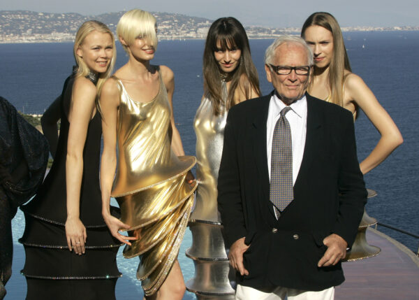 Pierre Cardin stands with models