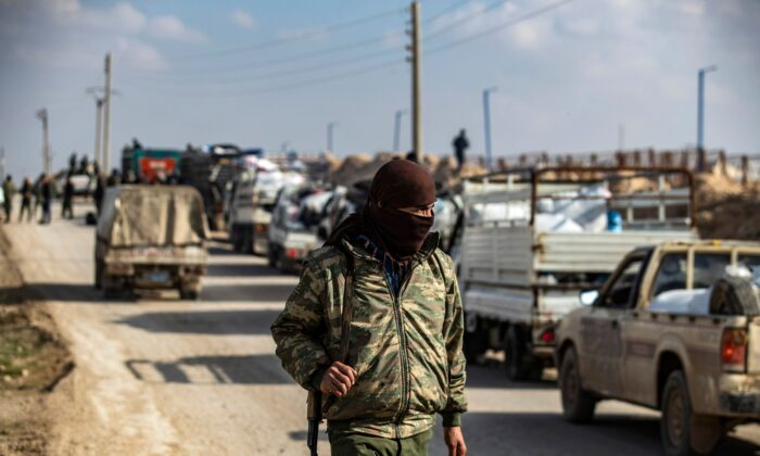An internal security patrol member stands in front of a convoy of trucks transporting Syrian women and children suspected of being related to the ISIS terrorist group, at the Kurdish-run al-Hol camp, in the al-Hasakeh governorate in northeastern Syria, on Dec. 21, 2020. (Delil Souleiman/AFP via Getty Images)
