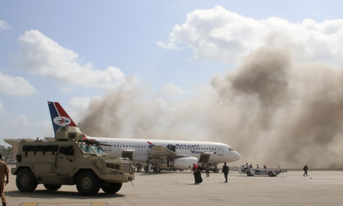 A military vehicle is seen on the tarmac as dust rises after explosions hit Aden airport, in Aden, Yemen, on Dec. 30, 2020. (Fawaz Salman/Reuters)