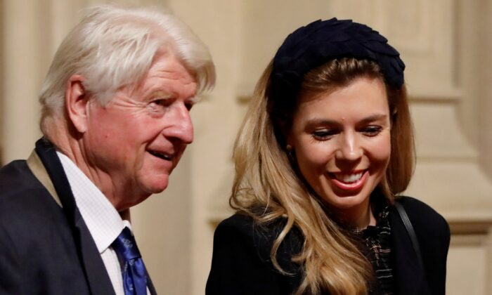 Stanley Johnson, the UK prime minister's father, and Carrie Symonds, partner of Prime Minister Boris Johnson, are seen in the Peers Lobby as they attend the Queen's Speech during the State Opening of Parliament in the Houses of Parliament in London on Oct. 14, 2019. (Tolga Akmen/Pool via Reuters)