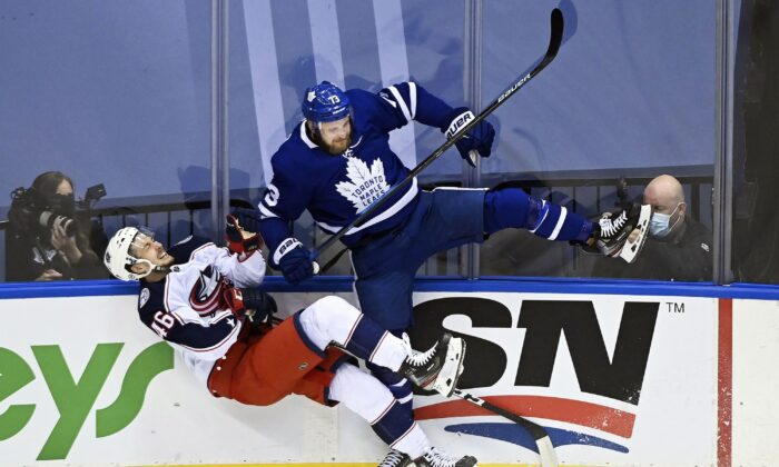 Hockey action between Toronto Maple Leafs left-winger Kyle Clifford and Columbus Blue Jackets defenceman Dean Kukan during the first period NHL Eastern Conference Stanley Cup playoffs in Toronto on Aug. 4, 2020. (The Canadian Press/Nathan Denette)