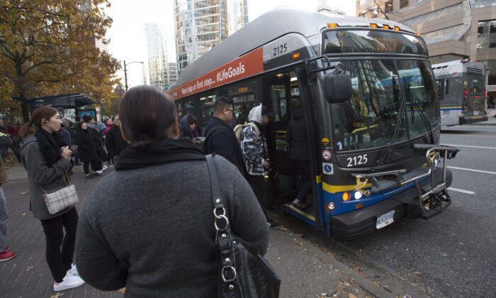 Passengers board a bus in downtown Vancouver, Canada, on Nov. 1, 2019. (Jonathan Hayward/The Canadian Press)