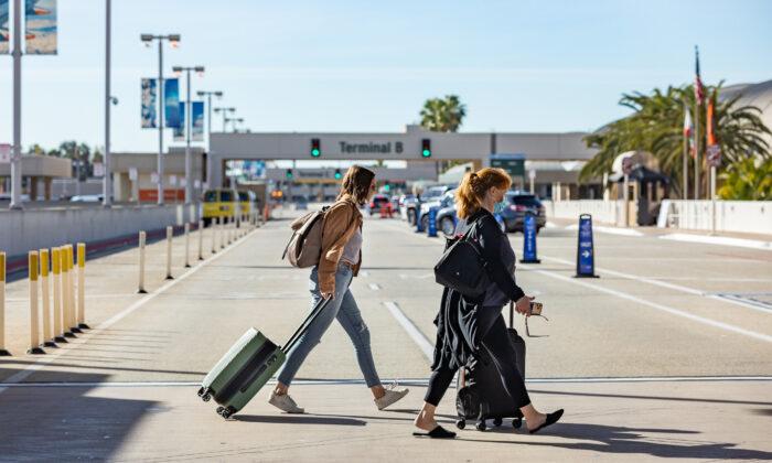 Travelers walk with thier baggage at John Wayne Airport, in Santa Ana, Calif., on Dec. 30, 2020. (John Fredricks/The Epoch Times)