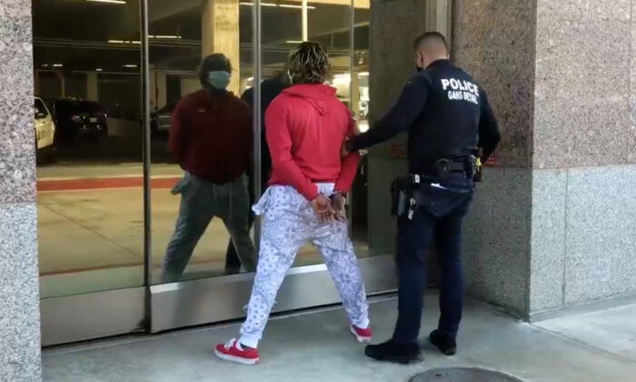 A Santa Ana police officer escorts kidnapping suspect Adrian Marcellus Alloway into the station in Santa Ana, Calif., on Dec. 29, 2020. (Screenshot/Twitter/Santa Ana Police Department)