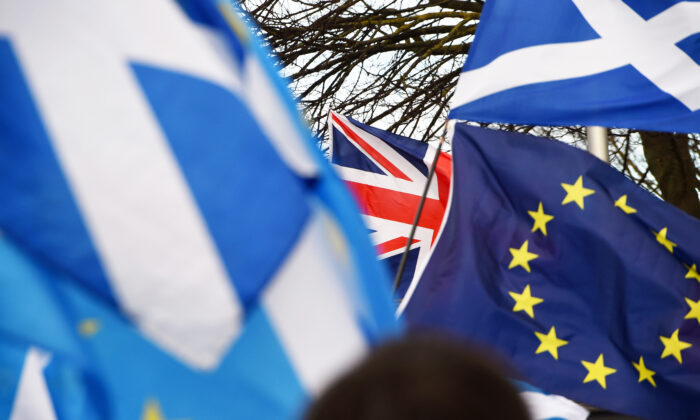 Pro-Union activists wave a Union flag (C) as Scottish Saltire and EU flags fly during an anti-Conservative government, pro-Scottish independence, and anti-Brexit demonstration outside Holyrood, the seat of the Scottish Parliament in Edinburgh on Feb. 1, 2020. (Andy Buchanan/AFP via Getty Images)